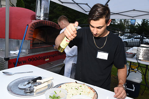 Zach Kahn making pizza for 900 Degree Brick Oven Pizza